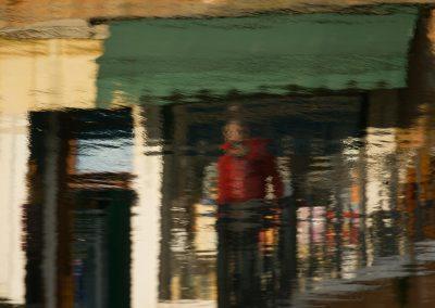 Frau mit roter Jacke vor Laden mit grüner Markise Venedig