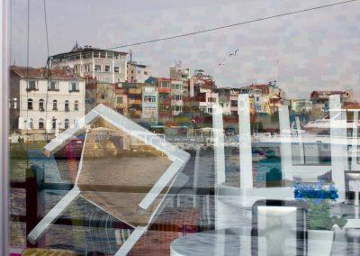 gespiegelte Häuserfront vor gestapelten Stühlen Istanbul